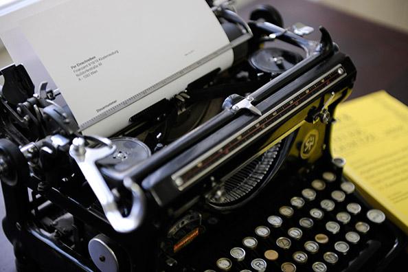 Alte Schreibmaschine, daneben am Tisch liegend ein Kodex Steuergesetze